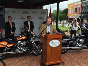 Tennessee Department of Tourist Development Commissioner Kevin Triplett, at podium, Putnam County Executive Randy Porter, back left, and Cookeville Mayor Ricky Shelton announce the Southern Backroads Harley Owners Group Rally event in 2017. UCBJ Photo/Jay Albrecht