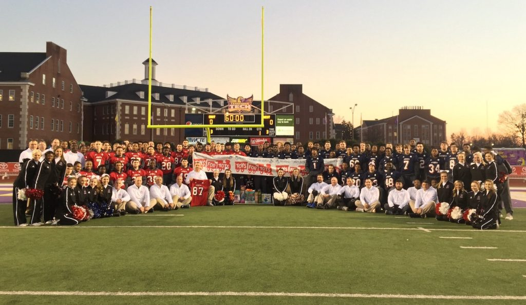 Toyota East vs. West All-Star participants pose at Tennessee Tech's Tucker Stadium with donations for Cookeville area Toys For Tots program.